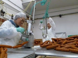 Employees at Field Roast in Seattle cut sausage links